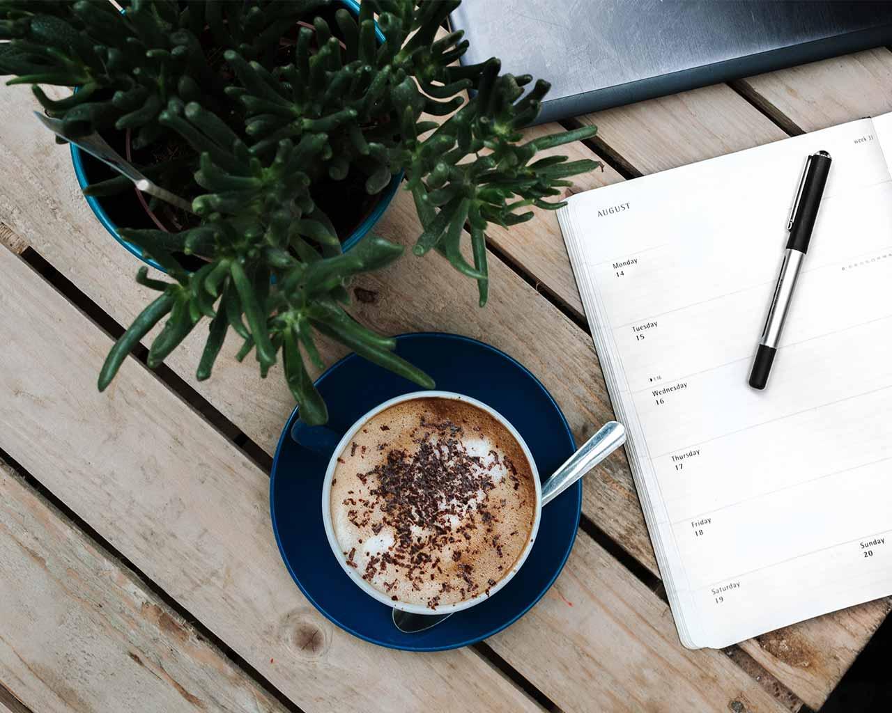 デスクに置いてあるコーヒーとノート